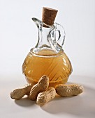 Groundnut oil in jug, peanuts in front