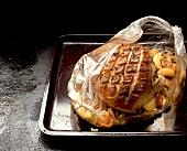 Pork roast in foil on baking sheet