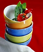 Pile of soup bowls with tomato, bay leaf and chilis