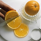 Squeezing orange half and cutting orange into slices