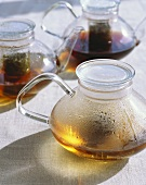 Three glass teapots with tea (half empty)
