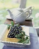 Kuchen mit frischen Heidelbeeren; Kaffeekanne im Hintergrund