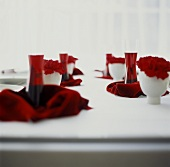 Laid table in white with Kir Royal & red carnations