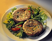 Two vegetable burgers on mixed salad