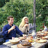 Couple in restaurant garden with light meal & wine