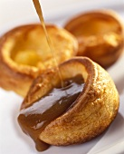 Fruit sauce being poured over Yorkshire pudding