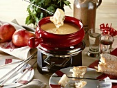 Cheese fondue in a red caquelon (fondue pan)