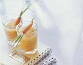 Banana and carrot drink in two glasses on exercise books