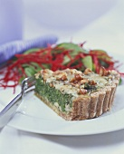 Piece of spinach quiche with cheese and walnuts