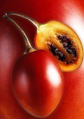 Whole and half tamarillo (tree tomato)