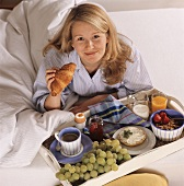 Breakfast in bed: woman with breakfast tray and croissant