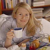 Breakfast in bed: woman with coffee cup and breakfast tray