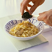 Slicing black truffle over tagliatelle