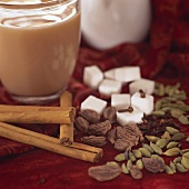 A glass of yogi tea, spices, sugar and milk jug beside it
