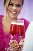 Junge Frau beim Anstossen mit Cocktail 'Prosecco Red'
