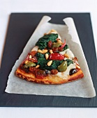 A piece of pizza with vegetables, cheese, pine nuts & raisins