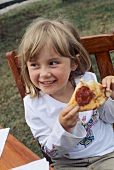 Girl eating pizza in open air