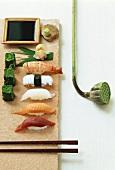 Various Nigiri sushi, pastes, soy sauce and lotus capsule