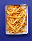 A bowl of chips on blue background