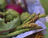 Still life with green asparagus and vegetables in basket