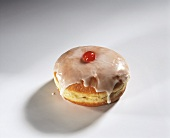 A doughnut with icing and cherry filling
