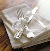 Silver cutlery with white bow on napkins