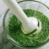 Mixing green herb sauce to a puree with hand blender