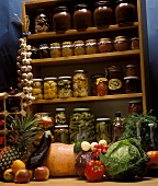 Pickles on a cellar shelf, vegetables and fruit in front