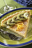 A piece of lemon & kiwi tart on dessert plate with fork