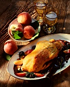 A roast duck with peach wedges and blackberries