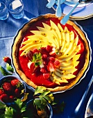 Tart with mango wedges on strawberry sauce & raspberries