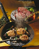 Beef tournedos with morels and sage in a frying pan