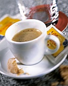 Expresso with sugar sachet & biscuit with bite taken