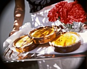Hands holding tray with crema catalana & carnations