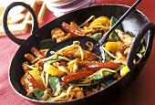 Finely chopped chicken with peppers & oranges in the wok