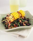 Spicy tuna and sweetcorn kebab on bean salad
