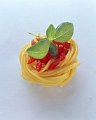 A spaghetti nest with diced tomatoes and basil