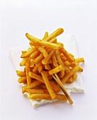 Pommes frites auf weisser Serviette und Holzspiesschen