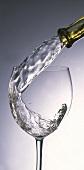 Weisswein aus der Flasche ins Glas eingiessen