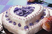 Two-tiered heart-shaped cake with candied violets