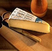 A piece of Fontina on a chopping board with knife