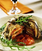 Aubergine charlotte with tomato sauce, a piece cut