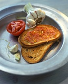 Toasted slice of bread with tomato and garlic sauce