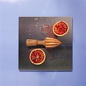 Halved blood orange and wooden lemon squeezer