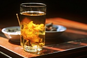 A glass of lotus tea with lotus blossom