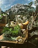 Rustikaler Holztisch mit Kräutern, Zwiebeln, Wein und Brot auf Terrasse mit Fernblick auf ein historisches Bergdorf