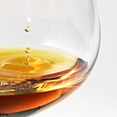 Cognac dripping into a brandy glass