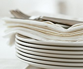 A pile of plates with napkins and cutlery