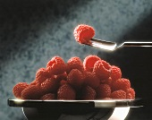 Raspberries in a bowl and one on a fork