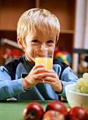 Small boy drinking a glass of orange juice